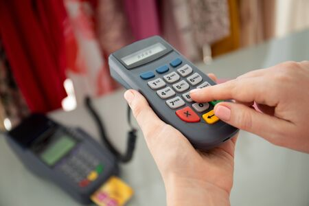 Woman enters pin code payment purchase pay pass online terminal in the store