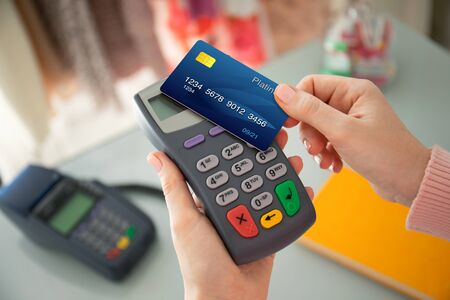 Woman hand holding plastic card and pay pass online terminal in the store Imagens