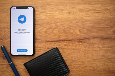 Anapa, Russia - August 1, 2019: iPhone X with social networking service Telegram on the screen and background wooden desk. iPhone was created and developed by the Apple inc. Editorial