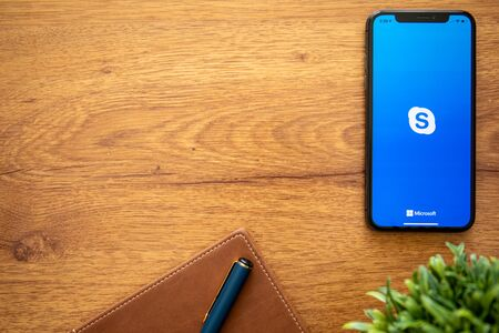 Anapa, Russia - August 1, 2019: iPhone X with calling Skype application and background wooden desk. iPhone was created and developed by the Apple inc.
