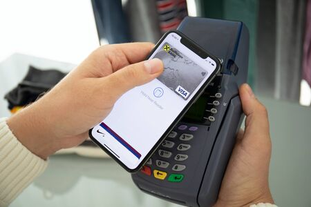 Anapa, Russia - August 12, 2019: Man hand holding iPhone X with Apple Pay on the screen and pay pass online terminal. iPhone was created and developed by the Apple inc. Editorial