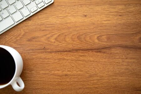 wooden table background with keyboard and a cup of coffee