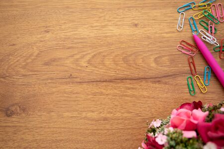 wooden table background with flower, paper clips and pen Imagens