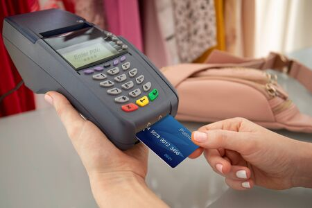 Woman hands holding plastic card and pay pass online terminal in the store