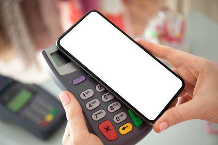 Achat de paiement femme pour téléphone avec écran isolé et terminal en ligne de carte de paiement dans le magasin