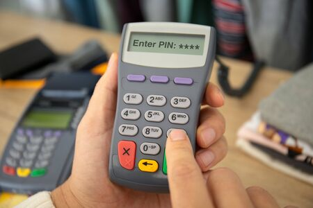 Man enters pin code payment purchase pay pass online terminal in the store Imagens