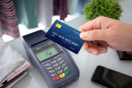 Man hand holding plastic card and pay pass online terminal in the store