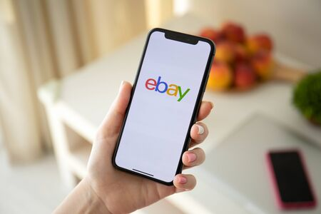 Anapa, Russia - July 22, 2019: Woman holding iPhone X with Internet shopping service eBay on the screen. iPhone was created and developed by the Apple inc.