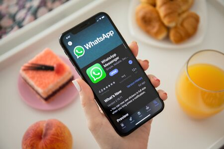 Anapa, Russia - July 23, 2019: Woman holding iPhone X with social networking service WhatsApp on the screen. iPhone was created and developed by the Apple inc.