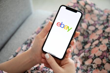 Anapa, Russia - July 23, 2019: Woman holding iPhone X with Internet shopping service eBay on the screen. iPhone was created and developed by the Apple inc.