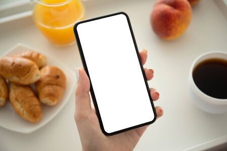 female hand holding phone with isolated screen in cafe at breakfast Imagens