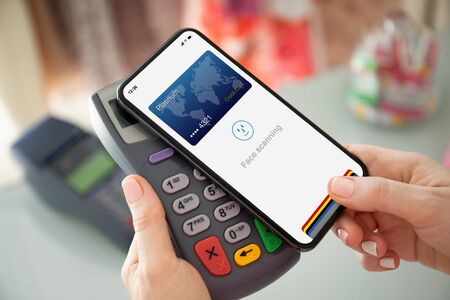 woman hand holding phone with face scanning id and payment purchase on pay pass online terminal