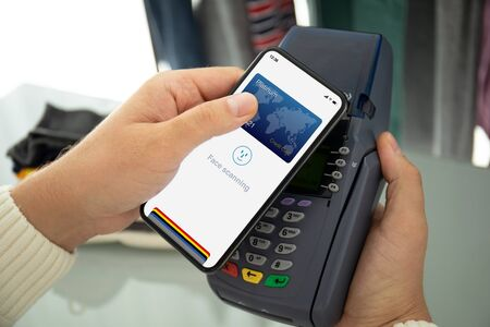 Man hand holding phone with face scanning id and payment purchase on pay pass online terminal Imagens