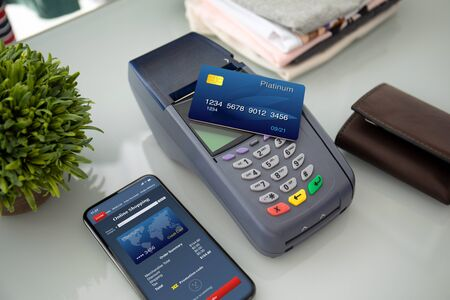 Plastic card payment purchase and pay pass online terminal and phone with online shopping on the screen Imagens