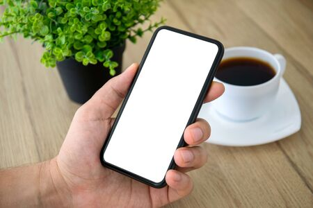 male hand holding phone with isolated screen over table in cafe