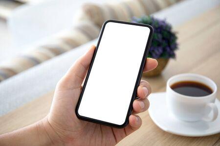 manos masculinas sosteniendo el teléfono con pantalla aislada sobre una mesa en la habitación