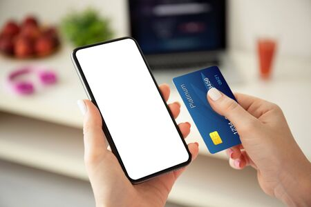 female hands holding phone with isolated screen and credit card on the background room