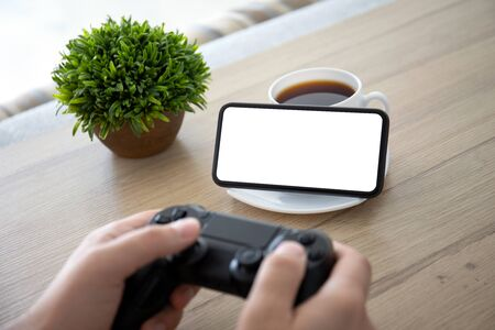 male hands holding joystick on background of phone with isolated screen