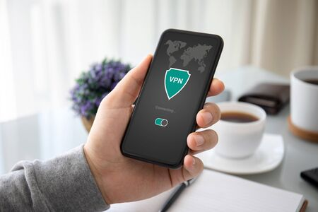 male hand holding phone with app vpn creation Internet protocols for protection private network over table in the office