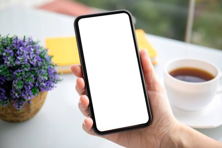 female hand holding phone with isolated screen over table in cafe
