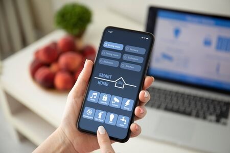 female hands holding phone with app smart home on the screen over a table with laptop in room