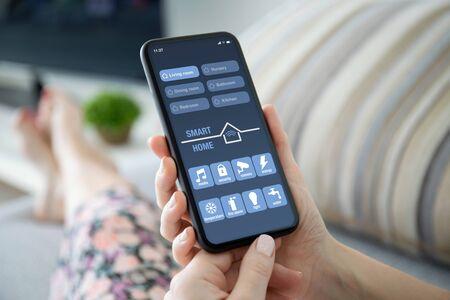 weibliche Hände, die Telefon mit App Smart Home auf dem Bildschirm im Zimmer auf dem Sofa halten Standard-Bild