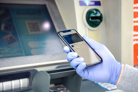 Alanya, Turkey - March 24, 2020: Man hand in disposable protective glove holding iPhone 11 with Apple Pay Cash on the screen at ATM.