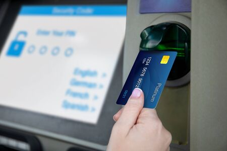 female hand holds credit card at ATM and password entry screen
