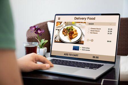 mains masculines sur clavier d'ordinateur portable avec application de livraison de nourriture à l'écran