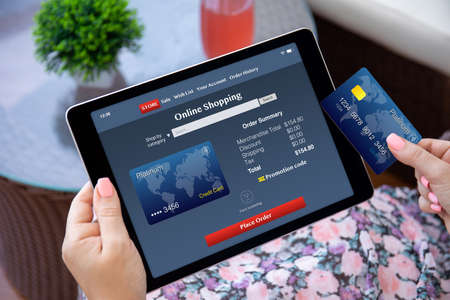 female hands holding computer tablet with app online shopping on screen and plastic credit card