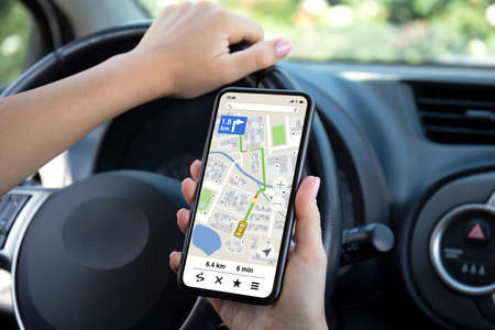 female hands driving car holding phone with navigator app on the screen Stockfoto