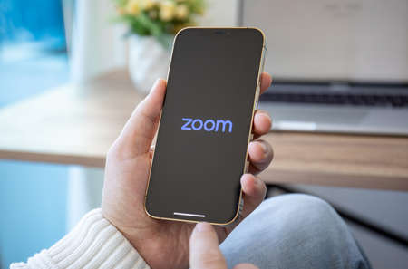 Alanya, Turkey - December 16, 2020: Man hands hold Apple iPhone 12 Pro Max Gold with calling Zoom Video Communications application. Redactioneel