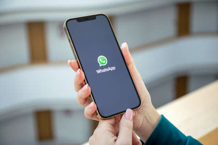 Alanya, Turkey - December 18, 2020: Woman hands hold Apple iPhone 12 Pro Max Gold with messenger WhatsApp on the screen. Redactioneel