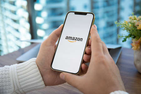 Alanya, Turkey - December 16, 2020: Man hands holding iPhone 12 Pro Max Gold with online Internet shopping service Amazon on the screen.