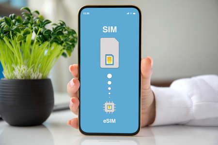 female hand holding phone with Sim card replacement on eSim in room house Stockfoto