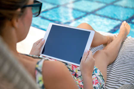 woman hands holds white computer tablet with blue screen near the pool