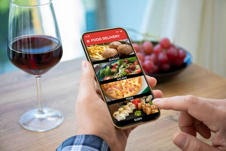 male hands hold phone with food delivery app over table with glass of wine and fruit