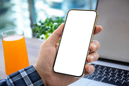 male hand holding golden phone with isolated screen on table with laptop in office