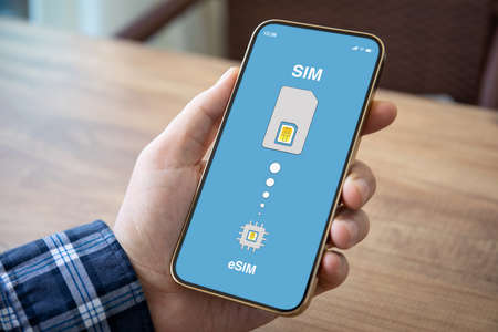 male hand holding phone with Sim card replacement on eSim