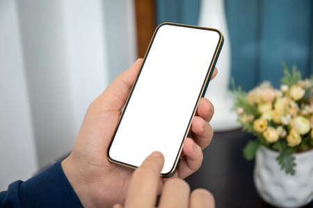 man holding gold phone with isolated screen in hands in room home Stockfoto