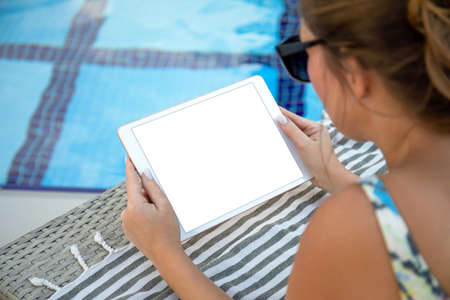 woman in hands holds computer tablet with isolated screen near the pool