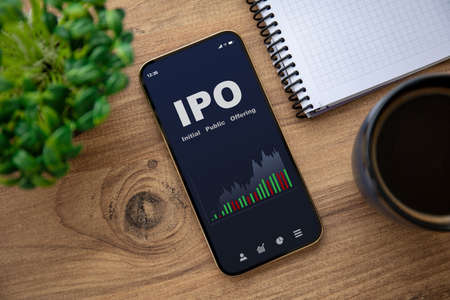 golden phone with IPO stocks purchase app on the screen on wooden table in office