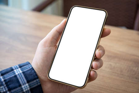 male hand holding golden phone with isolated screen over wooden table