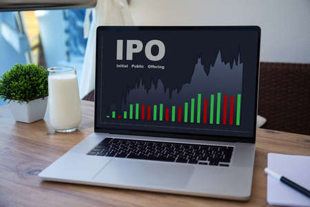 computer laptop with IPO stocks purchase app on screen table in cafe
