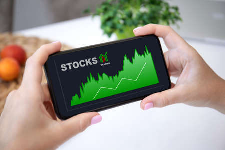 female hands hold phone horizontally with stocks trading app on the screen
