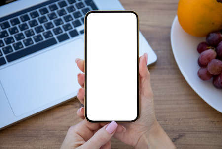 female hand holding golden phone with isolated screen on wooden table in office