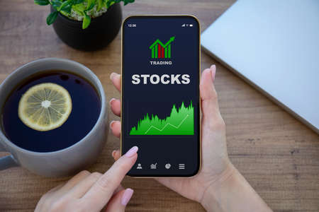 female hands hold phone with stocks trading app on the screen over table in office