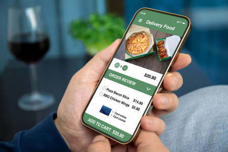 male hands hold phone with food delivery application background room in house