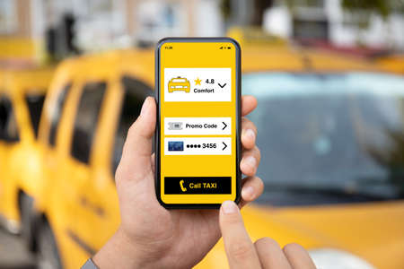 man hands holds phone with taxi call application on screen against background of yellow cars