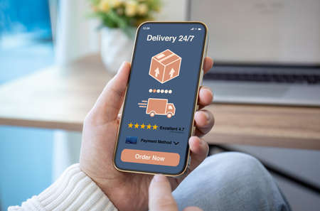 male hands hold phone with parcel delivery application on screen against background of room in house